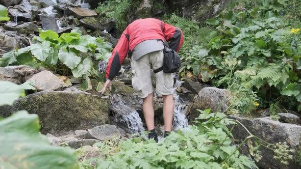 Tourist Collects Water in a Plastic Bottle From a Mountain Stream. Hiking Adventure