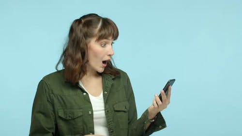 Slow Motion of Funny Young Woman Reading Smartphone and Looking Surprised Pointing Finger at Mobile