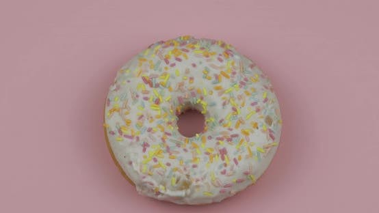 Thumbnail for Sweet Donut Rotating on Pink Background. Top View. Tasty, Fresh Sprinkled Donut