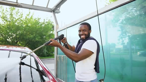 Thumbnail for African American which Looking at Camera while Washing His Own Car with High Water Pressure