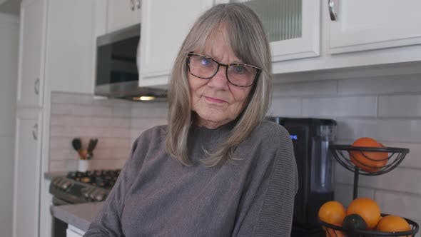 Grey haired senior woman with glasses looking at camera in her kitchen