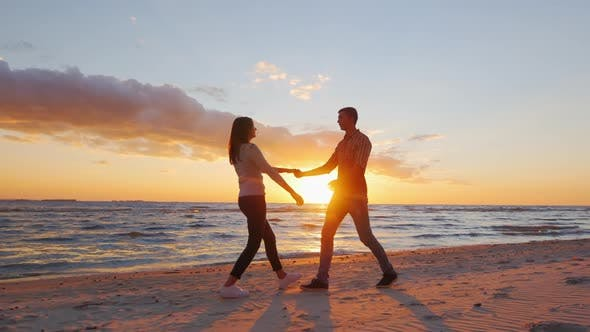 Thumbnail for Steadicam Slow Motion Shot: Romantic Couple Walking on the Beach at Sunset, Holding Hands, Having a