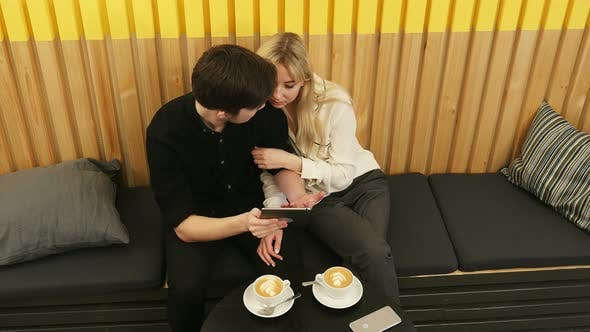 Thumbnail for Cheerful Couple Sitting at Coffee Shop and Websurfing on Tablet