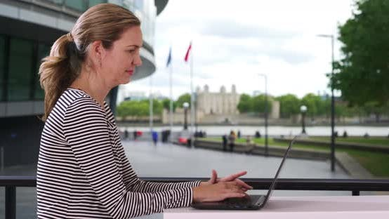 Thumbnail for London businesswoman typing on laptop outside
