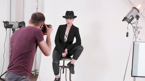 Handheld Shot of Model with a Hat on a Chair Posing to the Photographer