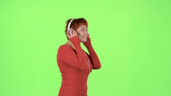 Thumbnail for Red Haired Woman Listening To Music on Headphones. Green Screen