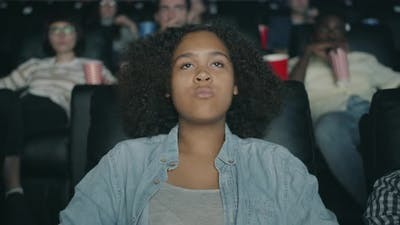 Sad African American Girl Watching Drama in Cinema with Sadness and Compassion
