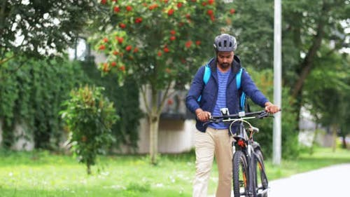 Delivery Man with Bag and Bicycle Walking in City