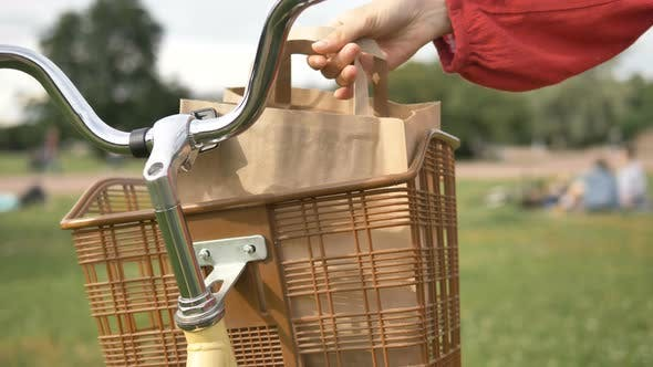Thumbnail for Woman Takes Out a Paper Bag of Food From a Vintage Basket on a Bicycle in a Park, Takeaway Delivery