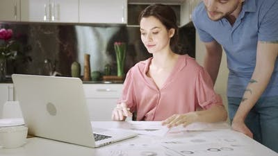 A Married Couple are Working Together at Home