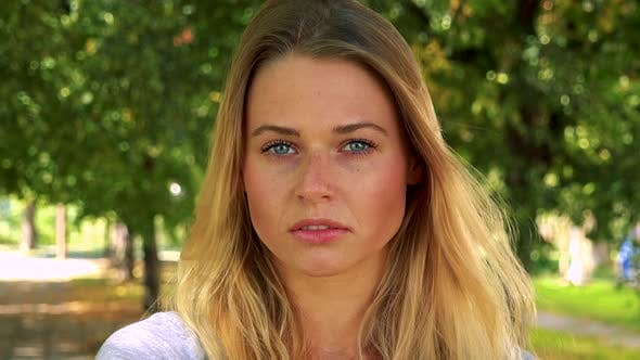 Thumbnail for Young Pretty Blond Woman Looks To Camera with Serious Face - Park with Trees in Background - Closeup