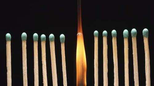Burning of single matchstick between row of new matchsticks