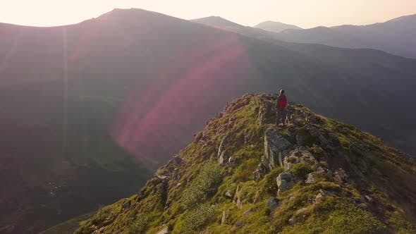 Hiker standing on top of rocky mountain enjoying magnificent view. Mountaineer looking at sunrise