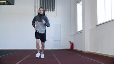 Focused Young Man in Sportswear Running Indoors
