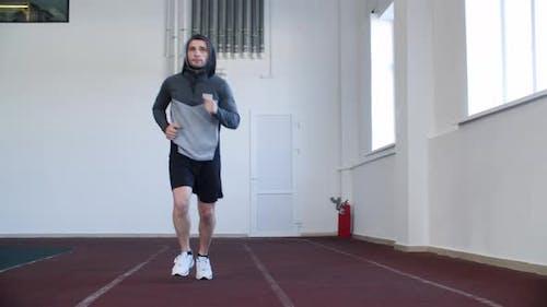 Konzentrierter junger Mann in Sportbekleidung läuft drinnen