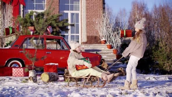 Two Funny Teenage Girls Sledding on Christmas Tree While Holidays. Happy Girlfriends with Christmas