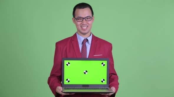 Thumbnail for Happy Asian Businessman Talking While Showing Laptop
