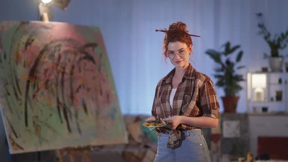 Female Painter Is Holding Paintbrushes and Palette Near Easel with Newly Painted Picture in Modern