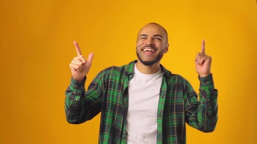 Cheerful Young African American Man Dancing with Joy Against Yellow Background