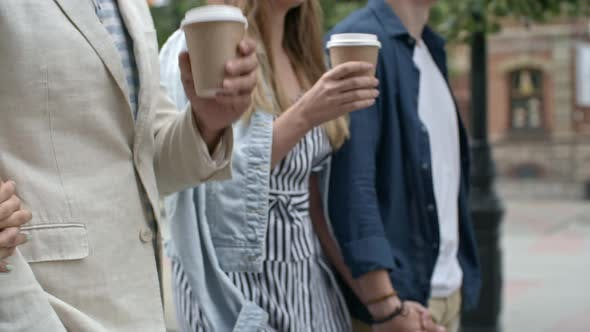 Thumbnail for Two Couples Walking with Coffee Cups