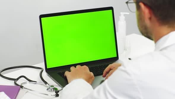Thumbnail for Doctor Reading Online on Chromakey Laptop
