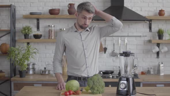 Thumbnail for Handsome Thoughtful Good-looking Man in the Shirt Standing at the Table with a Blender