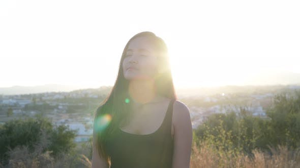 Thumbnail for Young Beautiful Asian Tourist Woman Thinking And Smiling On Top Of The Hill