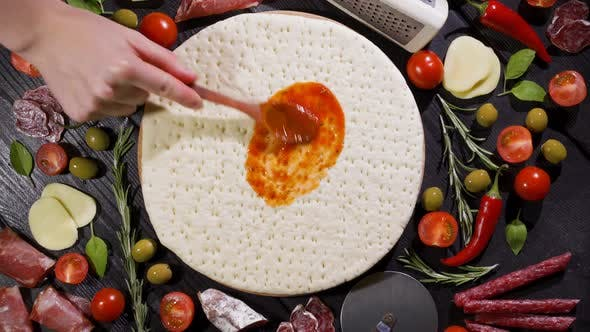 Top View of Making a Pizza with Ingredients Appearing on the Baking Plate