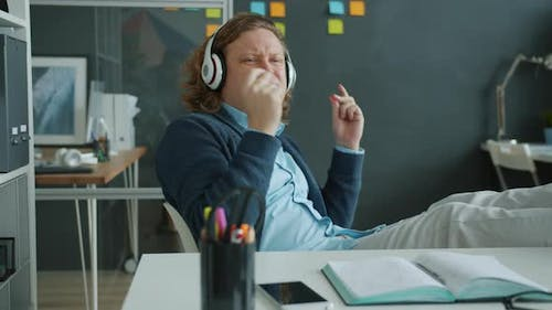 Slow Motion of Happy Businessman Listening To Music Enjoying Song in Office