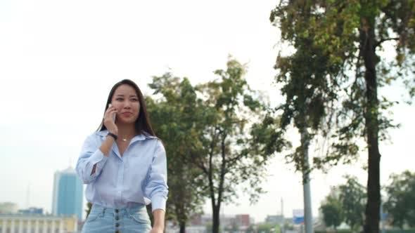 Thumbnail for Young Asian Lady Walking and Talking on Cell Phone