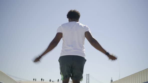 Thumbnail for Rear View of African American Sportsman Skipping Rope on Bridge