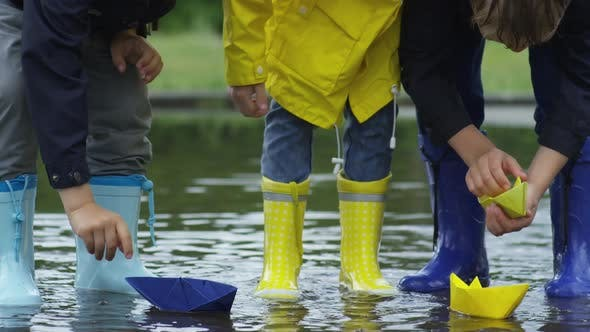 Thumbnail for Children Putting Paper Boats in Puddle