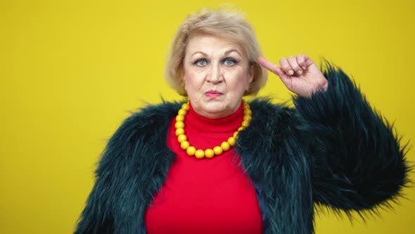 Thumbnail for Portrait of Annoyed Irritated Senior Woman Showing Nuts Gesture on Yellow Background
