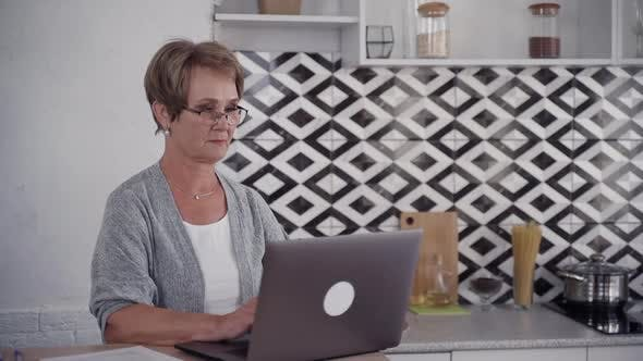 Thumbnail for Senior Woman Is Sitting at the Table and Working Using Digital Computer Technology.
