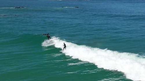 Aerial Shot Male Surfer Catches and Ride a Massive Barreling Waves