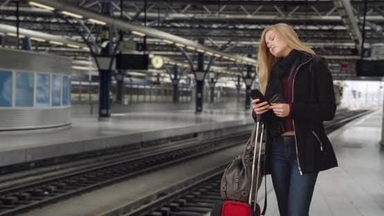 Thumbnail for Reisen junge weiße Frau wartet auf Zug am Bahnhof ankommen