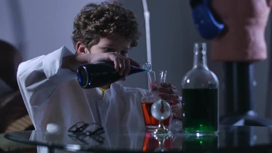 Thumbnail for Side View of Caucasian Boy Mixing Multi-colored Liquids in Flasks. Curly-haired Teenage Genius in