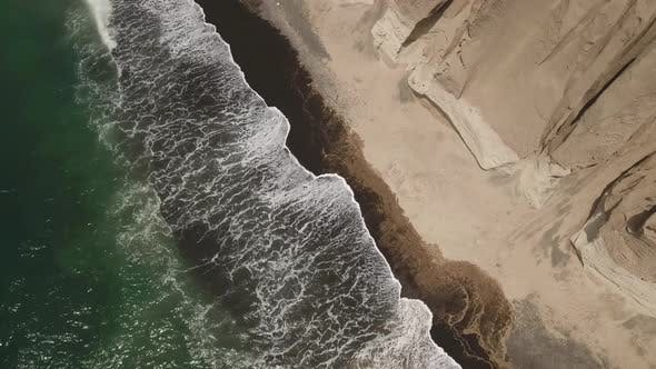 Waves on the black sand beach of Santorini in Greece - aerial view