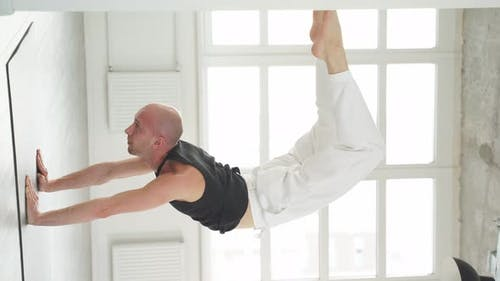 Professional Yogi Man Doing Scorpion Yoga Pose in Bright Studio Room