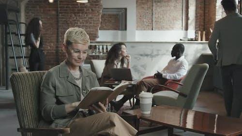Geschäftsfrau blickt durch Planer und posiert nach Kamera