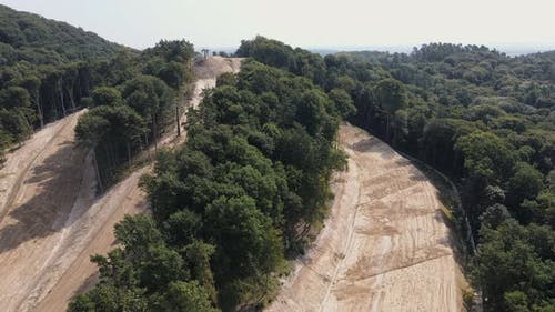 Aerial View Flight Over the Construction of a Ski Slope in the Summer. The Slopes of the Hill Are