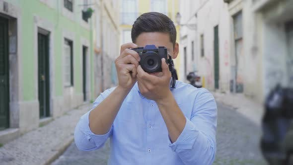 Cover Image for Focused Young Photographer Taking Pictures on Street