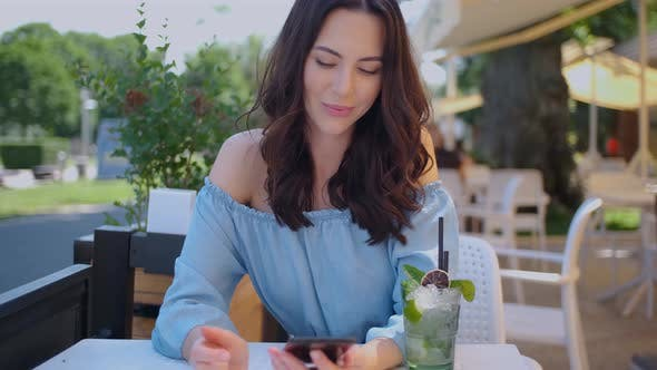 Cover Image for Pretty Brunette Woman Sitting in Outdoor Restaurant and Using Her Mobile Phone