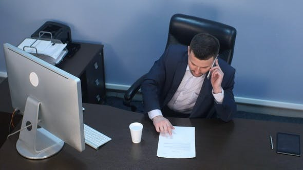 Thumbnail for Businessman talking on phone and working on computer in office