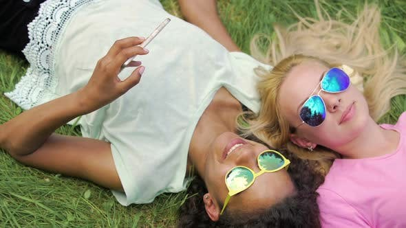 Thumbnail for Pretty Mixed Race Girl Showing Photos on Smartphone to Her Friend, Weekend