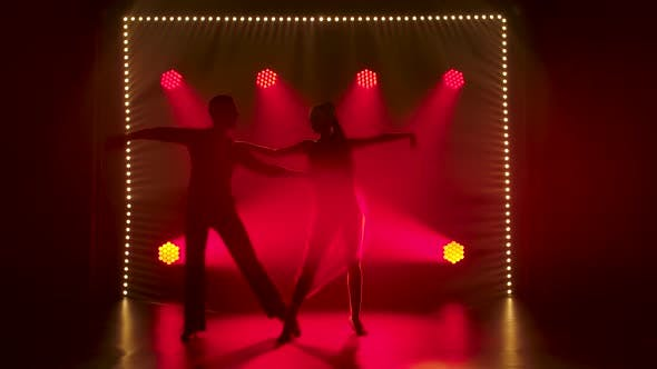 A Romantic Couple of Ballroom Dancers Are Dancing in the Studio Against the Background of Red