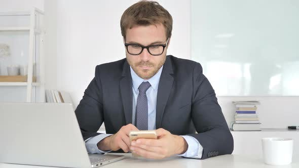 Businessman Using Smartphone at Work