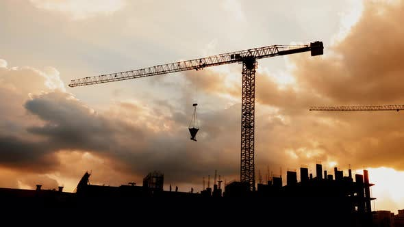 Thumbnail for Silhouette of Tower Cranes Working on Construction Site Residential Golden Hour, Warm Cloudy Sky