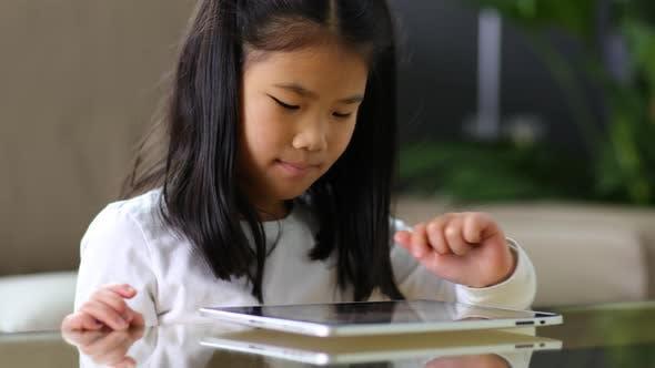 Thumbnail for Young Asian girl using digital tablet