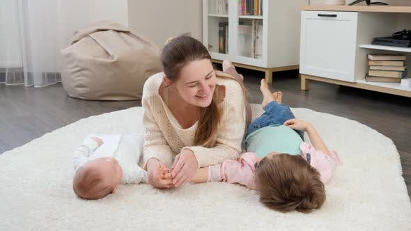 Cute Baby and Older Boy Lying with Smiling Mother on Carpet in Living Room